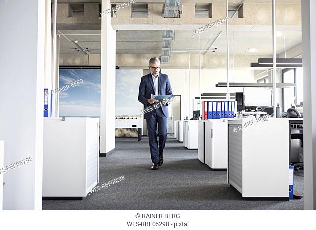 Businessman walking in office holding documents