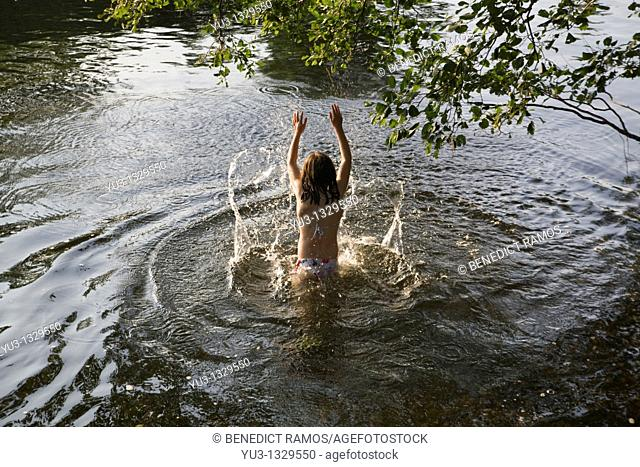 Young girl in a river splashing water