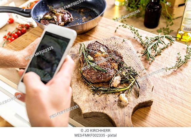 Man taking celll phone picture of prepared steaks