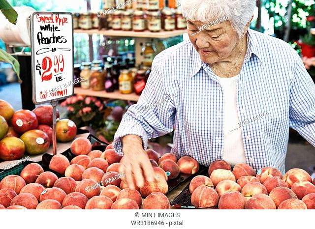 Senior woman standing at stall with fresh white peaches at a fruit and vegetable market