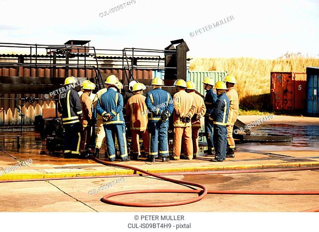 Firemen training, team of firemen listening to supervisor at training facility, rear view