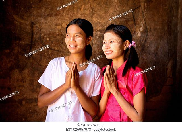 Two young Myanmar girls in a praying gesture