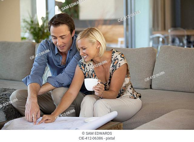 Couple examining blueprints on sofa
