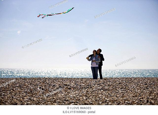 A pregnant woman and her partner flying a kite on the beach