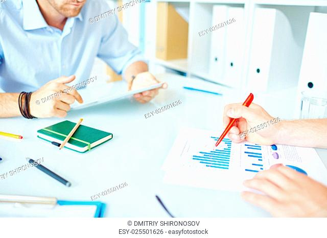 Businessman pointing at chart and graph in financial document with colleague working near by