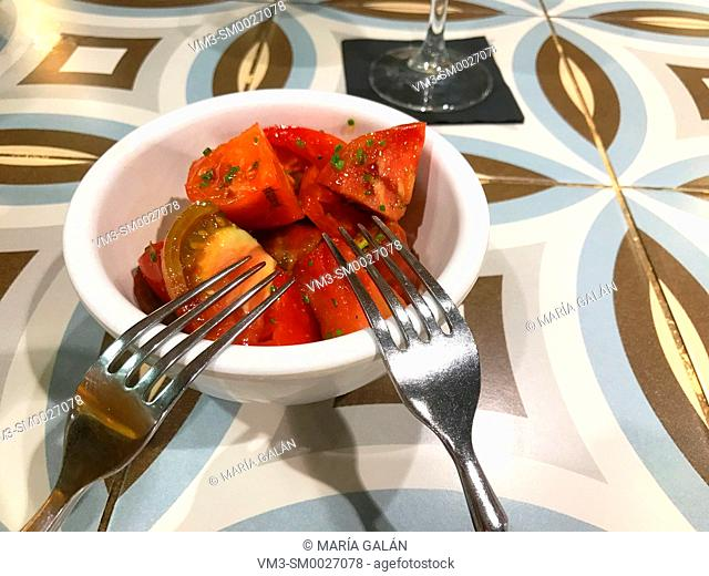 Tomato salad in a bowl with two forks