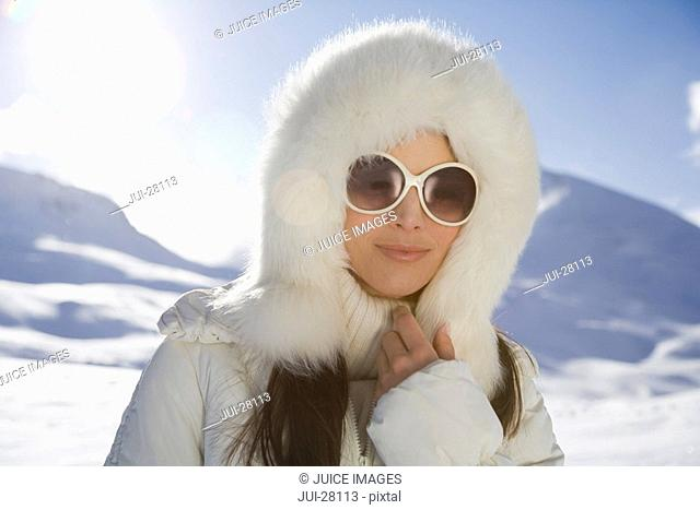 Portrait of young woman in fur hooded coat and sunglasses on winter day