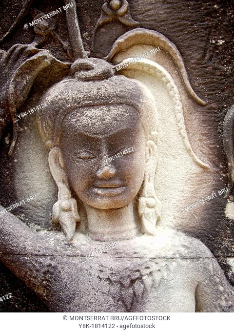 Stone carved female face with earrings, hairband and collar, Angkor Wat, Cambodia