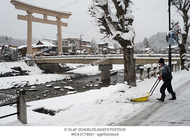 Takayama, Gifu, Japan, Asia - A man shovels snow on a road next to the Miyamae Bashi Bridge with the big Torii gate at one side that marks the entrance to a...