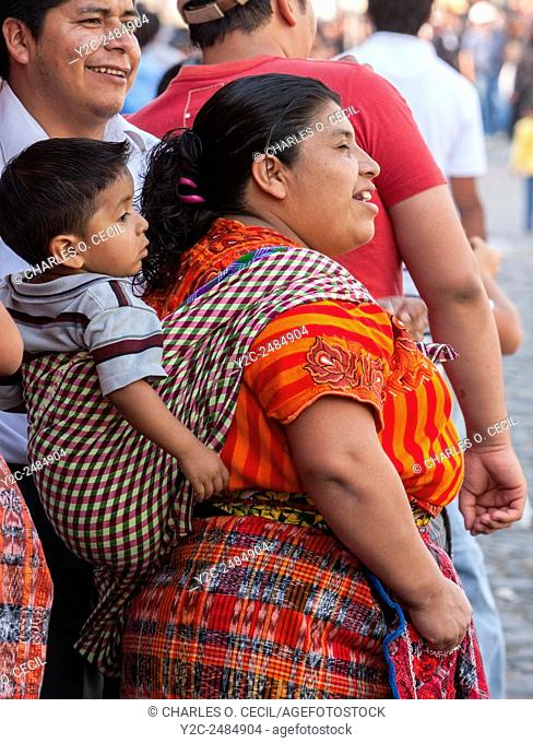 Antigua, Guatemala. Maya Mother in Traditional Clothing with Son on her Back. Semana Santa