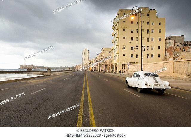 Cuba, Ciudad de la Habana province, La Havana, american car on the Malecon under a stormy sky