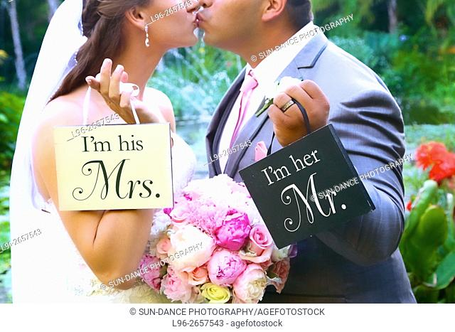 bride & groom kissing & holding 'Mrs. & Mr.' signs