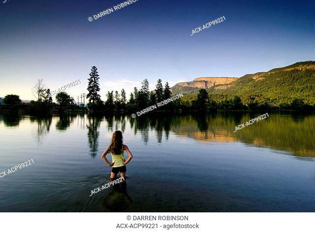 Young girl wading into the Shuswap River while watching the last light hit the Enderby Cliffs, in Enderby, in the Shuswap region of British Columbia, Canada