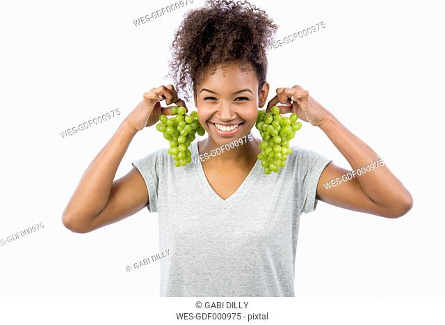 Portrait of smiling young woman holding green grapes like earrings in front of white background