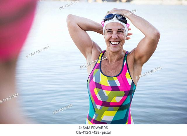 Portrait laughing, smiling female open water swimmer adjusting swimming cap in ocean