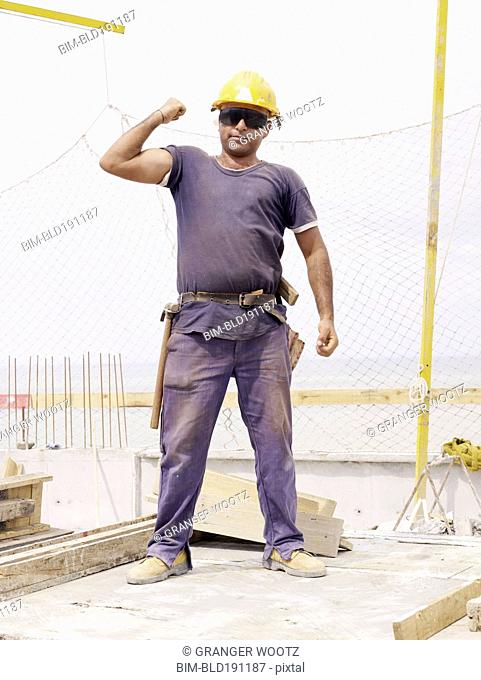 Hispanic worker flexing biceps on construction site