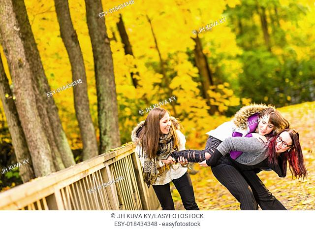 Three sisters play pranks on bridge and they have a fun together on autumnal park