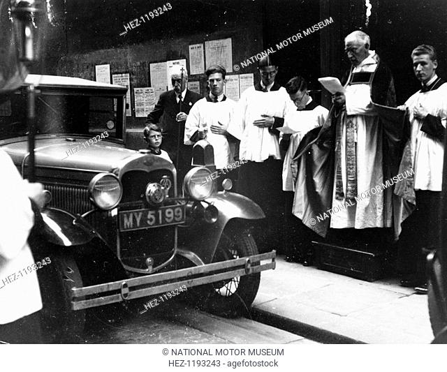 The blessing of cars, City of London, c1930. A priest conducts a blessing in front of a car. The ceremony takes place on July 20th, the feast of St Elias