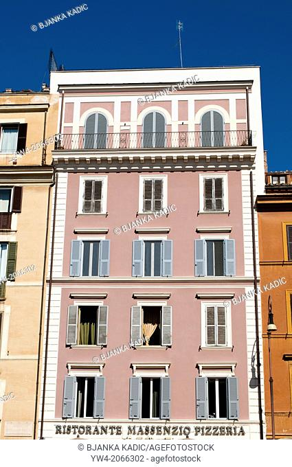 House painted in pink with blue window shutters on Via Cavour, Rome, Italy