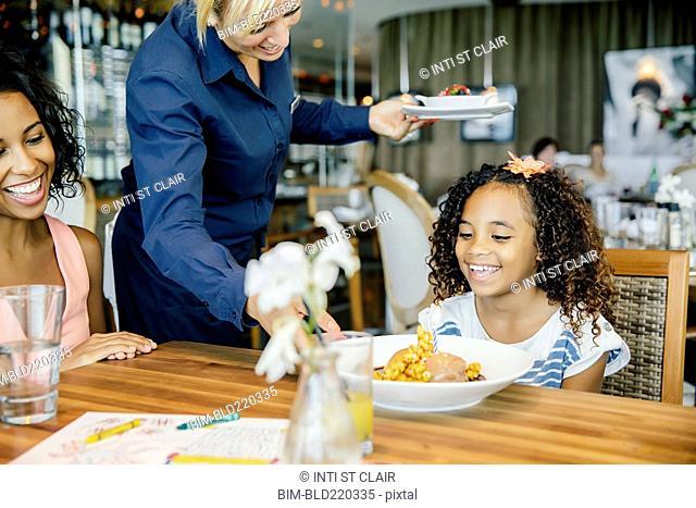 Server bringing birthday dessert to girl in restaurant