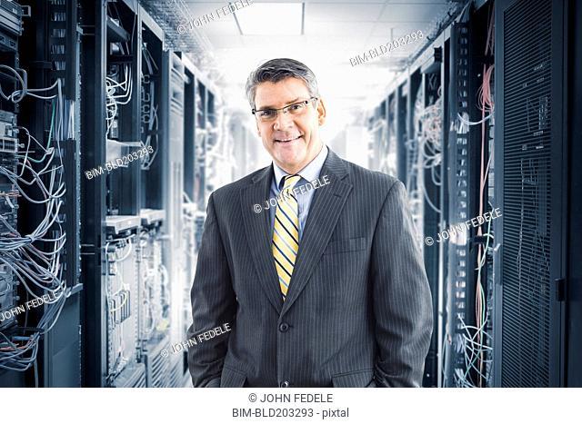Caucasian businessman smiling in server room