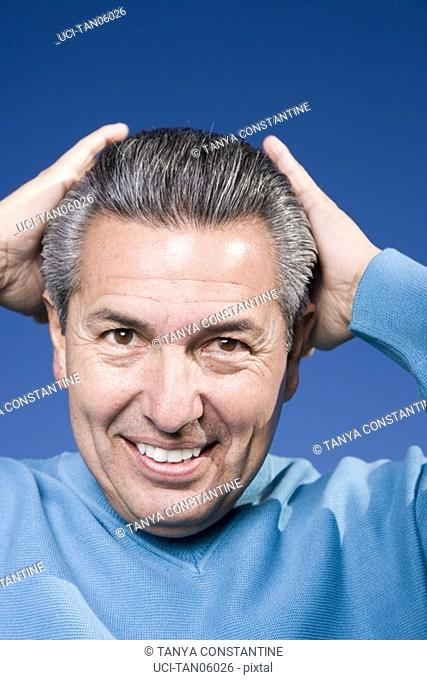Mature man holding head