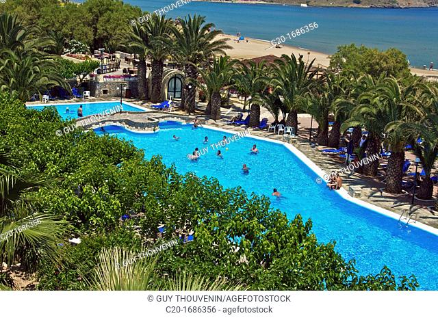 Tourists, at Hotel Mare Monte swimming pool, sea, and Saint Nicolas chapel in the background, Giorgioupolis, Crete, Greece
