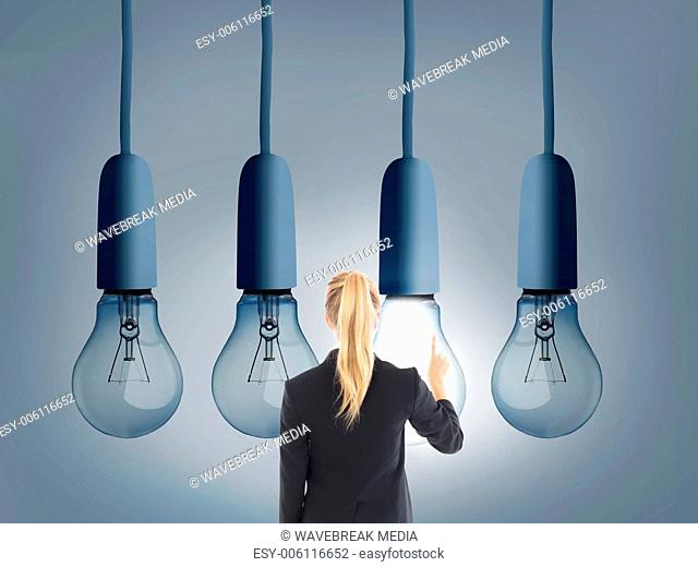 Blonde businesswoman pointing at huge light bulb
