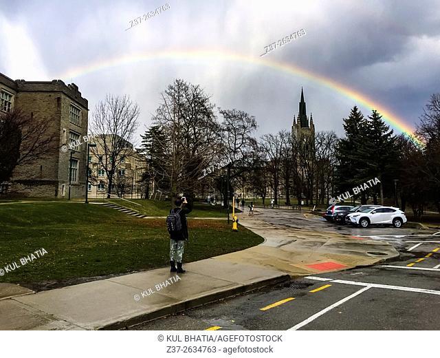 A young woman photographs a rainbow in an urban setting, Ontario, Canada