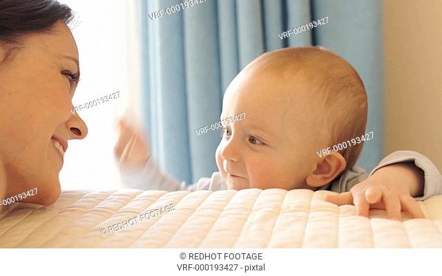 Mother and 12 month old baby playing on bed indoors