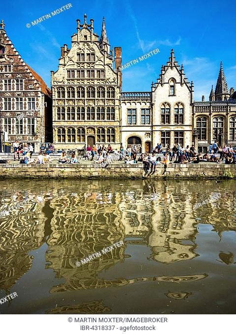 Leie River and promenade on the Graslei, with old guild houses and old post office, young people on the shore, Ghent, Flanders, Belgium
