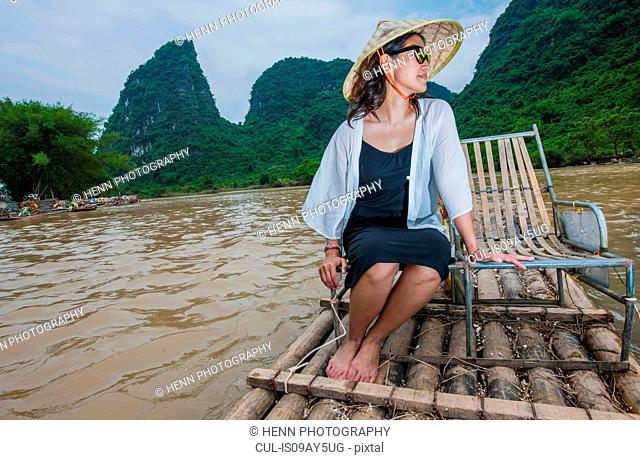 Woman with traditional straw hat sitting on a bamboo raft on the Yulong river in Guangxi, China