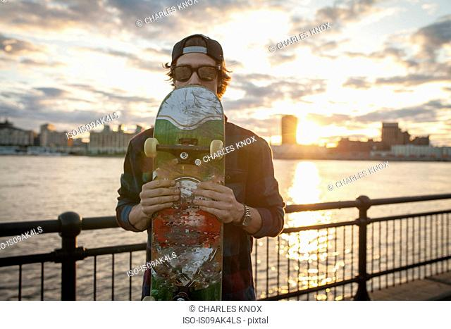 Portrait of young male skateboarder holding up skateboard on waterfront, Montreal, Quebec, Canada