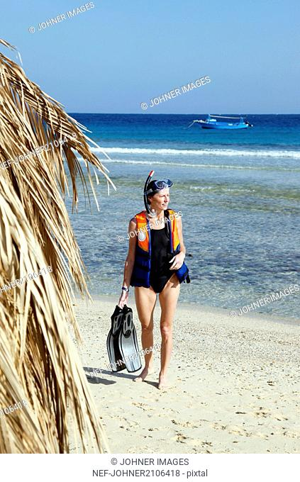 Woman holding diving equipment on sandy beach