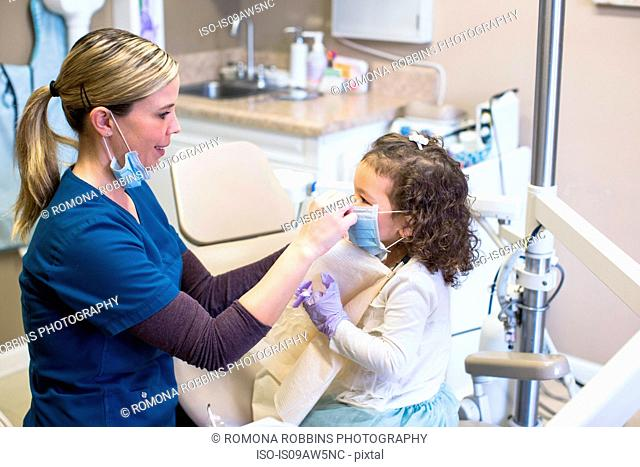 Side view of girl and dentist in dental office wearing surgical masks smiling