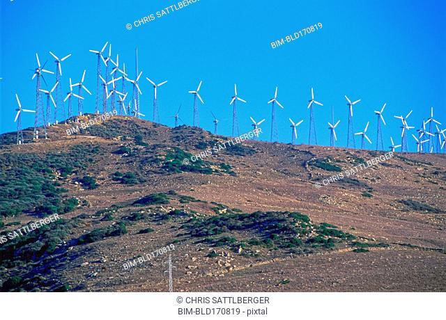 Wind turbines on hilltop in remote landscape