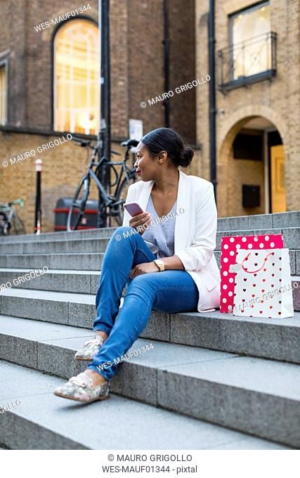 UK, London, woman with shopping bags and cell phone sitting on stairs in the city