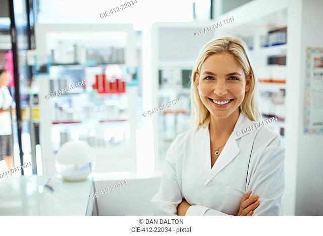 Pharmacist smiling in drugstore