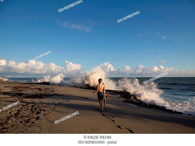 Rear view of boy exploring beach with splashing waves, Blowing Rocks Preserve, Jupiter Island, Florida, USA