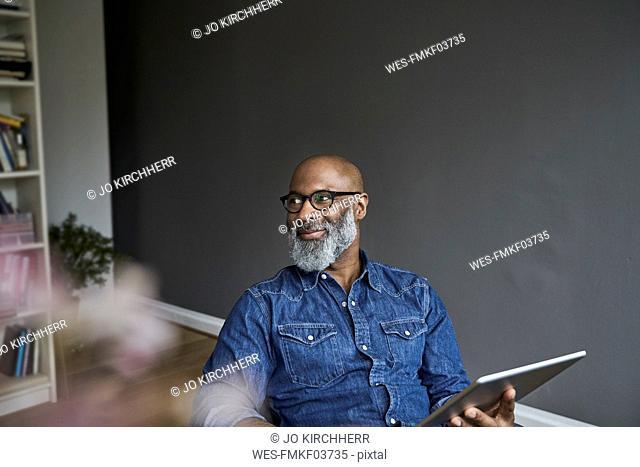 Mature man holding tablet, smiling