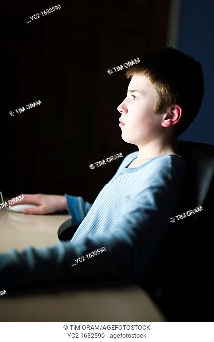 A 12 year old boy on his computer on Facebook internet website using very shallow depth of field