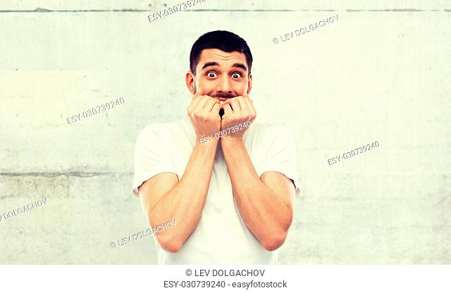 emotion, advertisement and people concept - scared man in white t-shirt over gray wall background