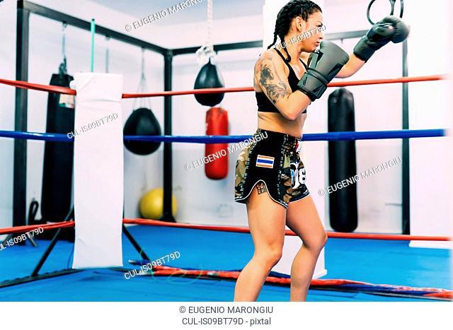Female boxer practising in boxing ring