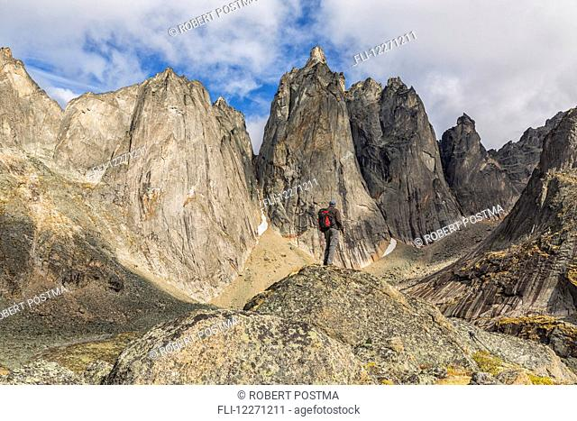 Man standing on a rock overlooking the granite jagged peaks of Tombstone Territorial Park; Yukon, Canada