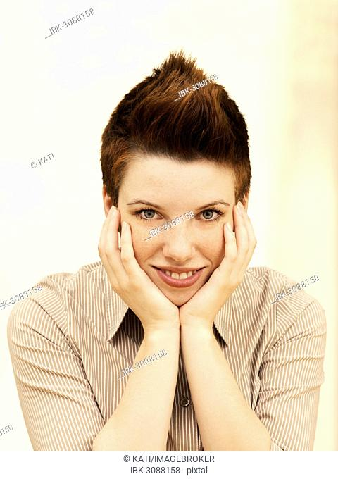 Businesswoman with a punk hairstyle, supporting her head in her hands, smiling