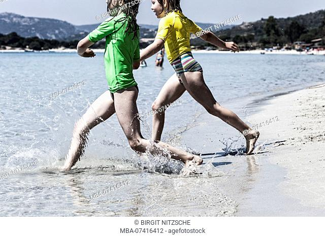 2 girls run into the crystal clear water on the beach of Porto-Vecchio Corsica