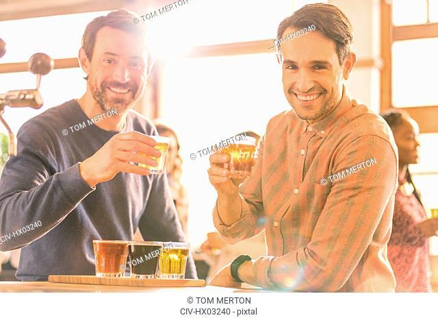 Portrait smiling men friends sampling beer at microbrewery bar