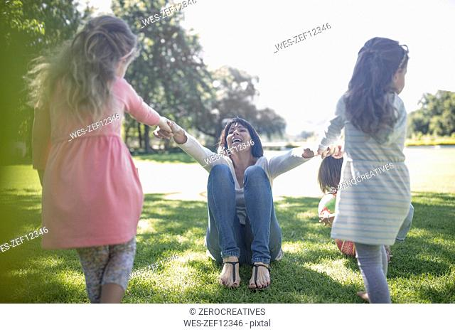 Two girls playing with their momther in park