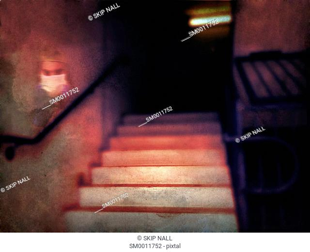A stairway leading upward with the image of a ghost on the wall