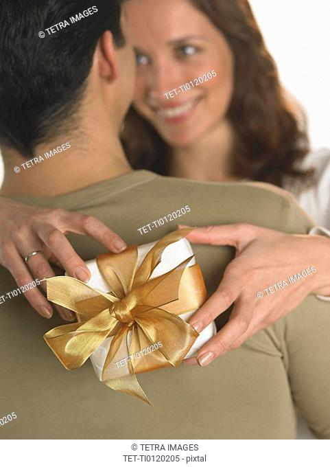 Woman holding gift with arms around man